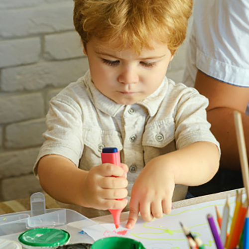 Serious boy draws. Young artist creates picture with pink felt-tip pen and paints. Multicolored pencils for creative education in school or kindergarten. Blond child on vacation, happy kid
